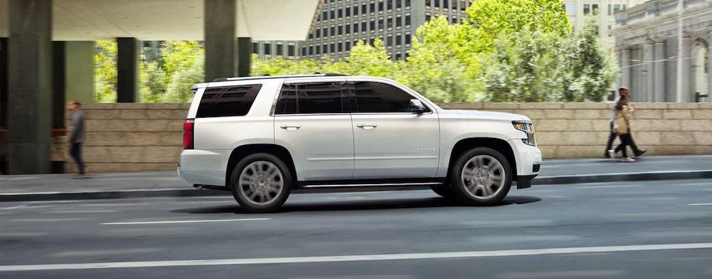 A white 2020 Chevy Tahoe is shown driving from the side on a city street.
