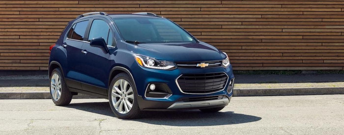 A blue 2019 Chevy Trax is parked in front of a wood wall near Fort Worth, TX.