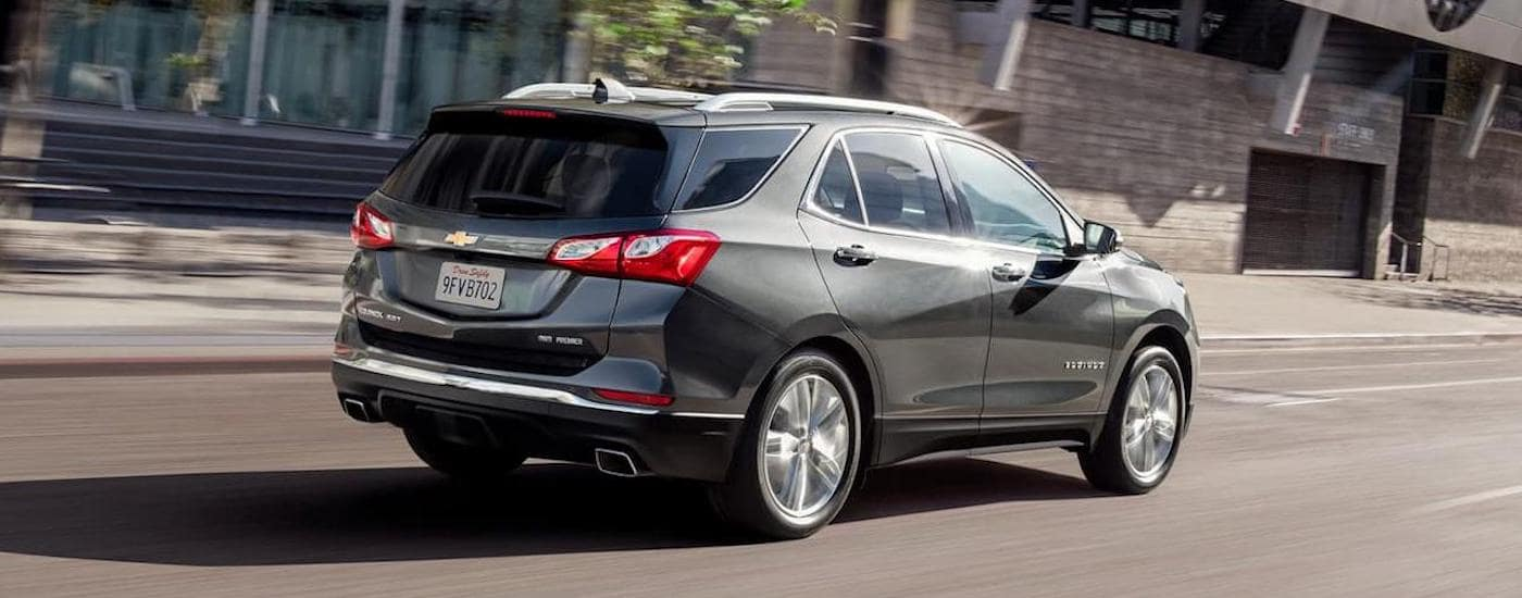 A grey 2020 Chevy Equinox is driving on a city street near Ennis, TX.