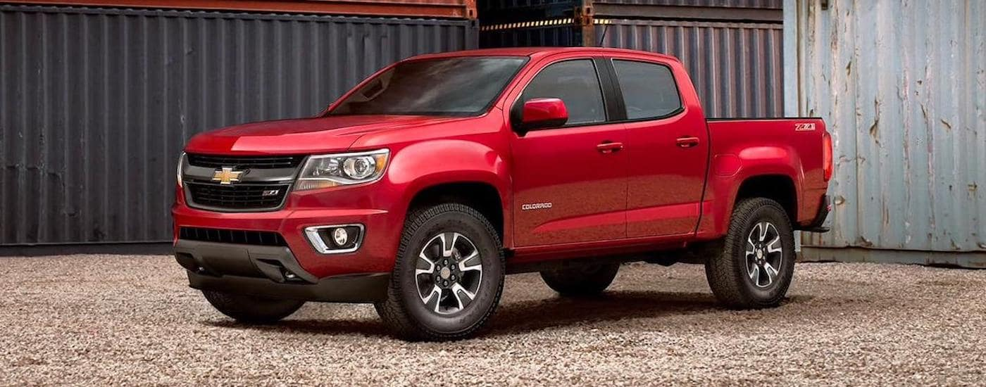 A red 2020 Chevy Colorado Z71 is parked in front of metal shipping containers outside Ennis, TX.