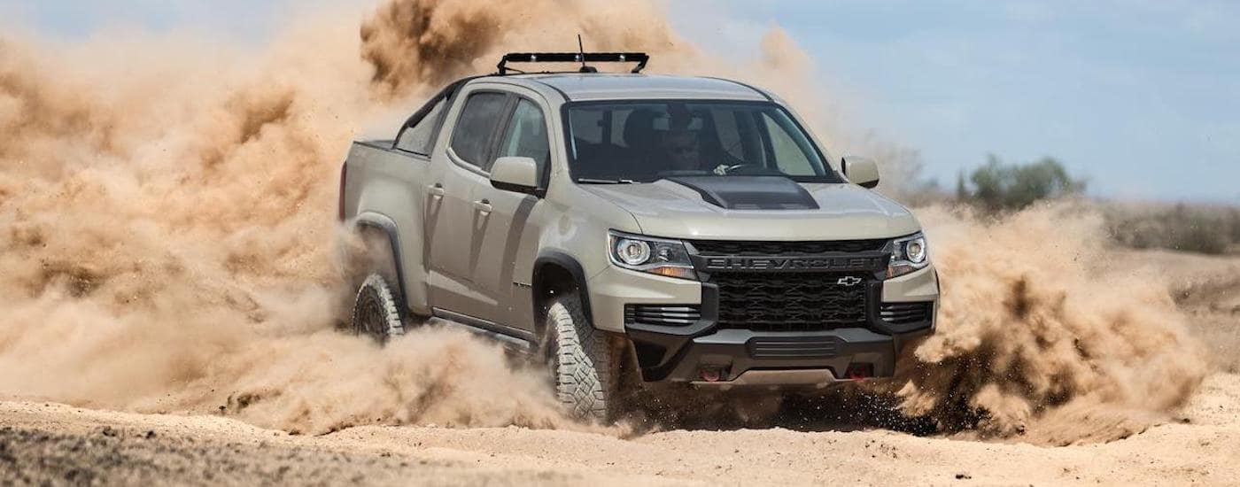 A beige 2021 Chevy Colorado ZR2, one of the new Chevy Trucks, is kicking up dirt on a trail outside Ennis, TX.