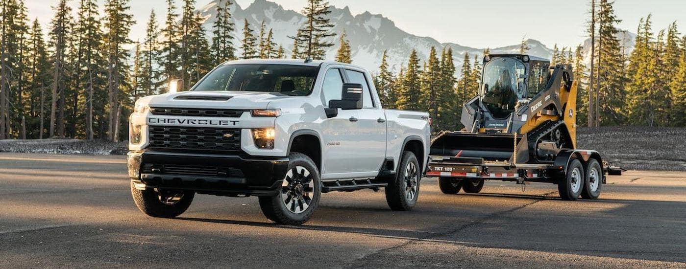 A white 2020 Chevy Silverado HD is towing a skid-steer loader in front of trees and mountains.
