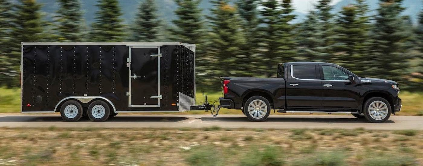 A black 2020 Chevy Silverado, one of our popular Chevy Trucks, is towing a large trailer in front of trees and mountains.