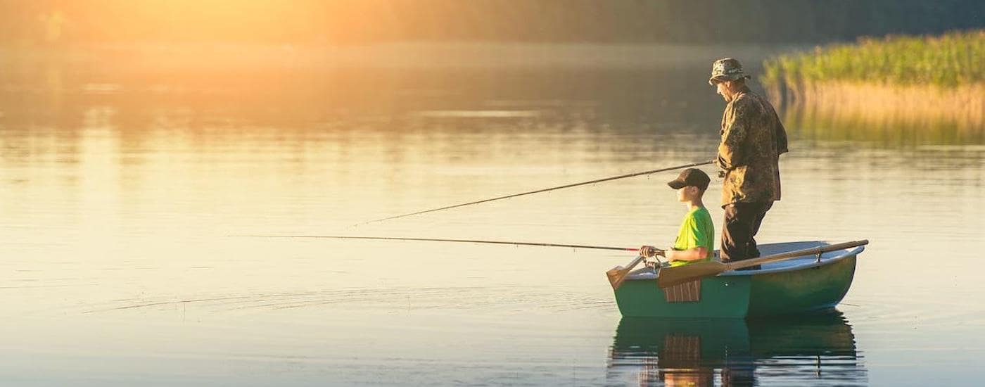 A father and son are shown fishing in a boat at dawn near Ennis, TX.