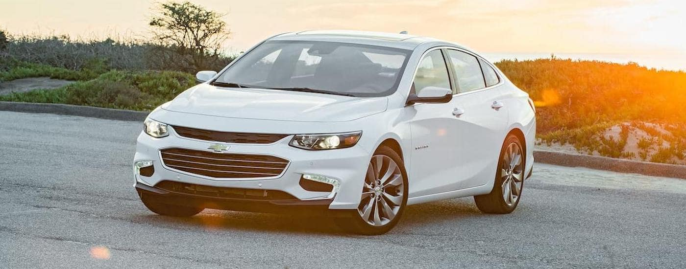 A white 2016 Chevy Malibu, one of the popular Chevy used cars in Ennis, TX, is parked in front of a setting sun.