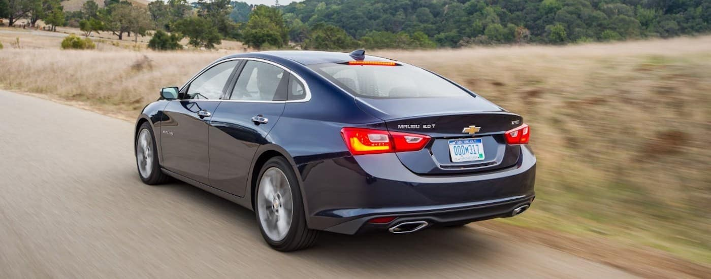 A dark blue 2018 Chevy Malibu is driving near Ennis, TX after being purchased through a Chevy Certified Pre Owned deal.