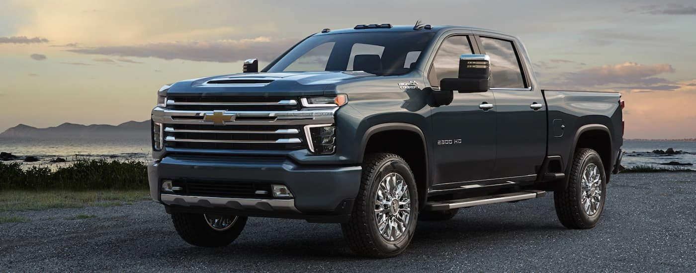 A dark blue 2020 Silverado HD, parked in front of a bay, will be one of the Chevy trucks for sale in Ennis, TX in late 2019.