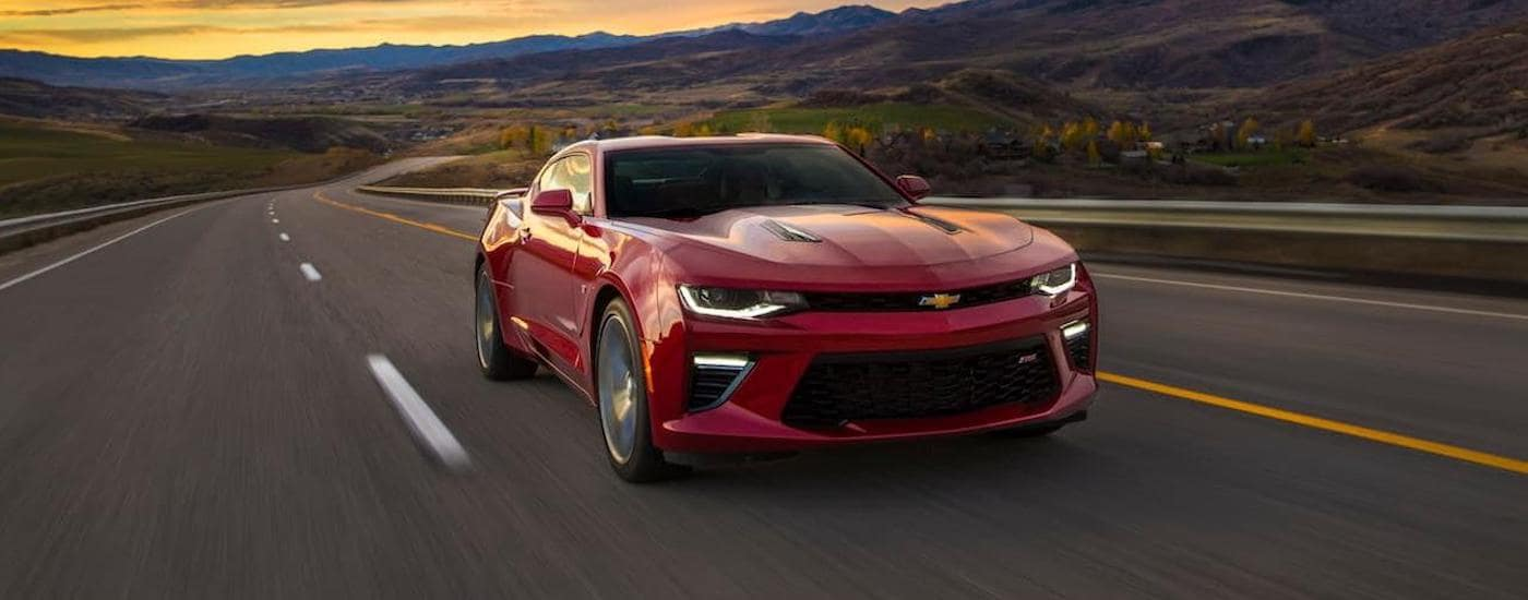 A red 2018 Chevy Camaro is driving on a highway near Ennis, TX, during sunset.