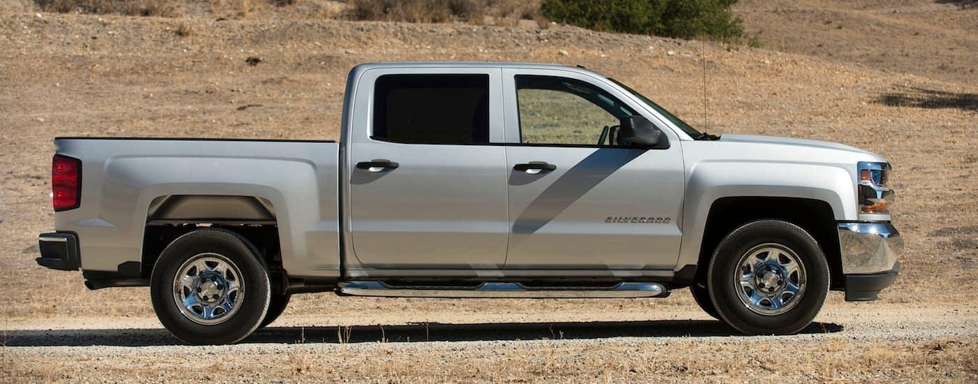 Used Chevy Trucks: A silver 2017 Chevy Silverado in a field.