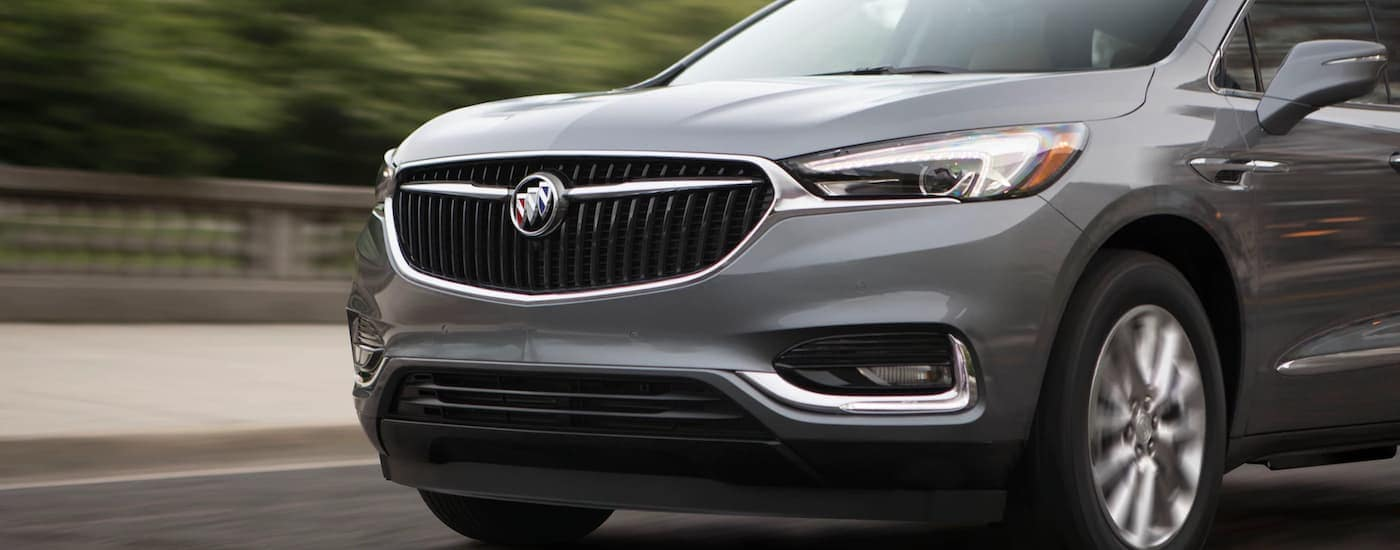 A popular Buick SUV, a grey 2020 Buick Enclave, which will be updated for the 2021 Buick Enclave, is driving past a blurred railing near Corsicana, TX.