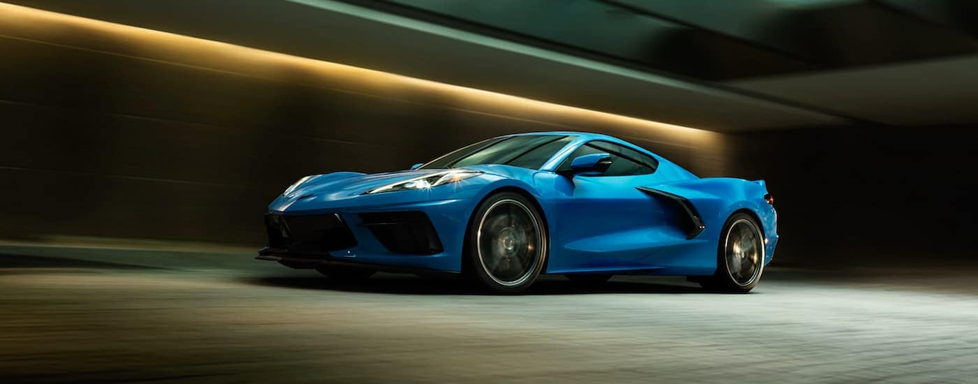 A blue 2020 Chevy Corvette is driving through a tunnel after leaving a Chevy dealership.