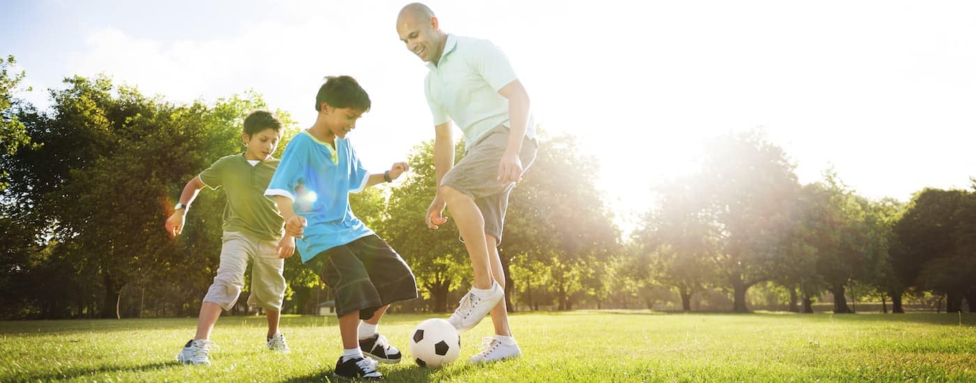 A father and sons are playing soccer at a Waxahachie, TX park.