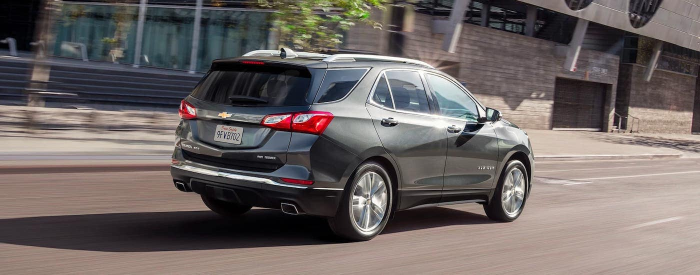 A gray 2020 Chevy Equinox is driving on a city street after leaving a Chevy dealership near Waco, TX.