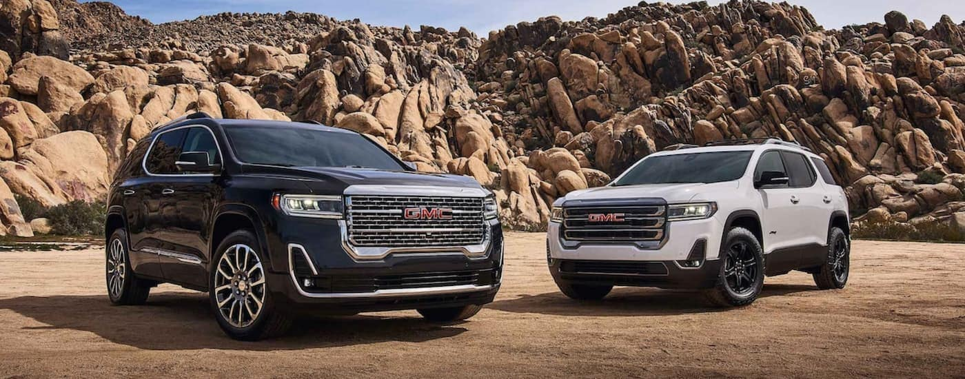 A black 2020 GMC Acadia is parked next to a white AT4 in front of a rocky hill after leaving a GMC dealer near Waco, TX.