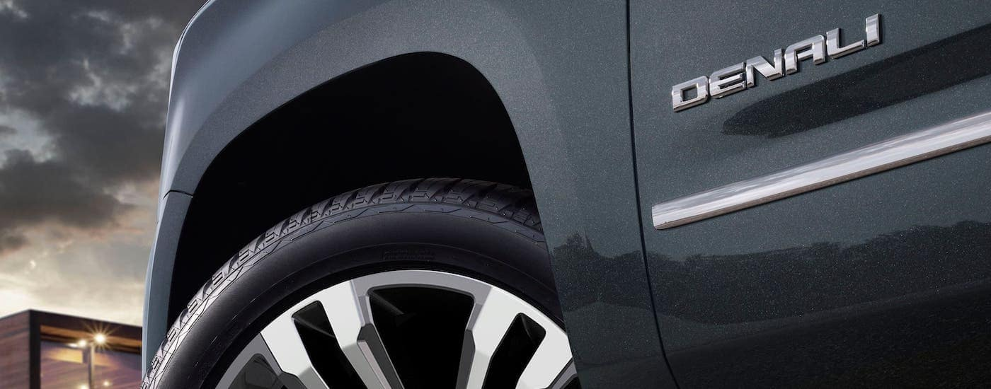 A closeup is shown of the side badging and front wheel on a metallic gray 2020 GMC Yukon Denali, find one at a GMC dealer near Waco, TX.