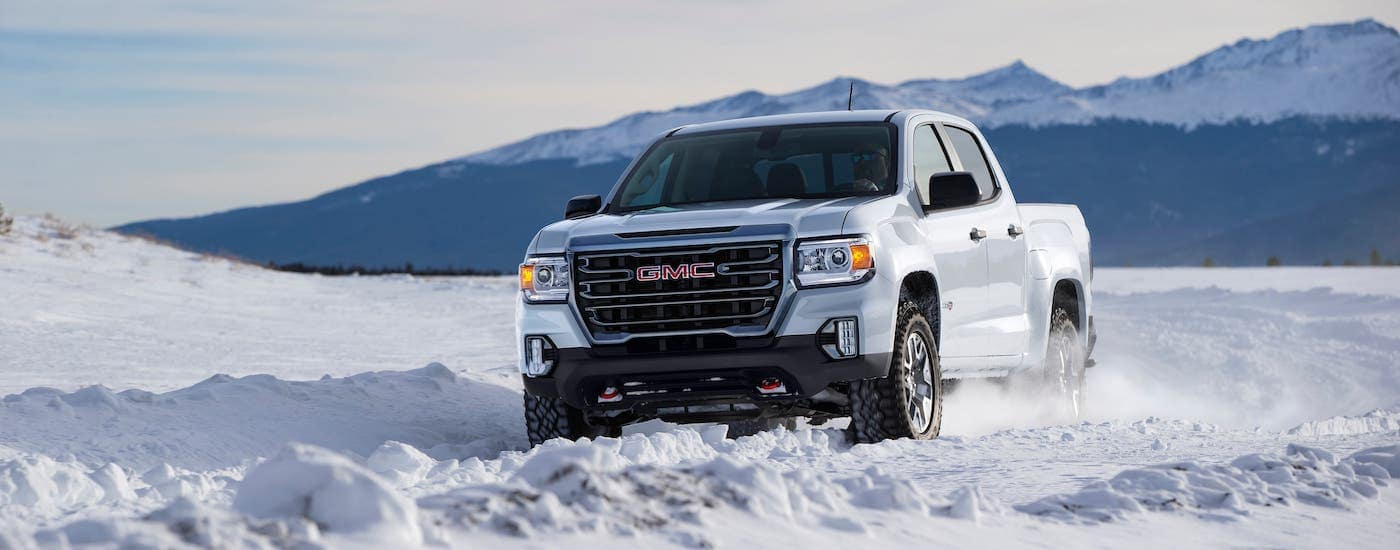One of the newest GMC trucks for sale at your local Corsicana dealer, a white 2021 GMC Canyon AT4, is shown on a snowy trail in front of mountains.