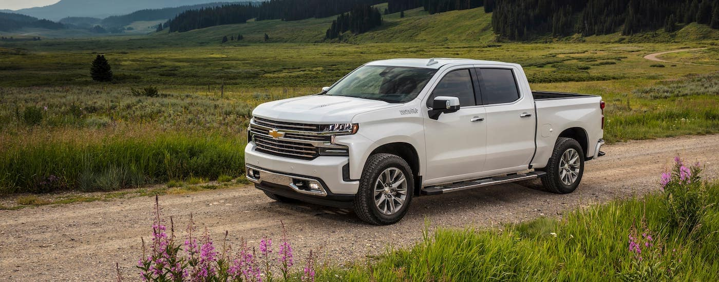 When comparing trucks for sale in Corsicana, TX, you may come across a white 2020 Chevy Silverado 1500 High Country, shown here driving on a dirt road in a field.