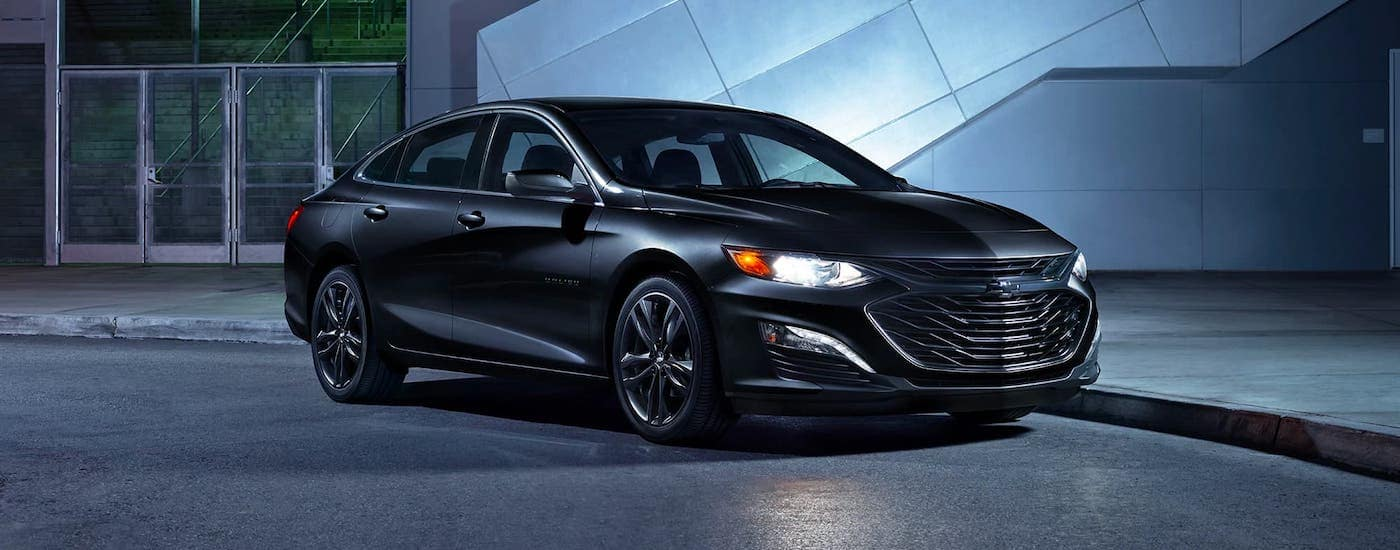 A popular Chevrolet around Fort Worth, a black 2020 Chevy Malibu is parked in front of a modern building at night.