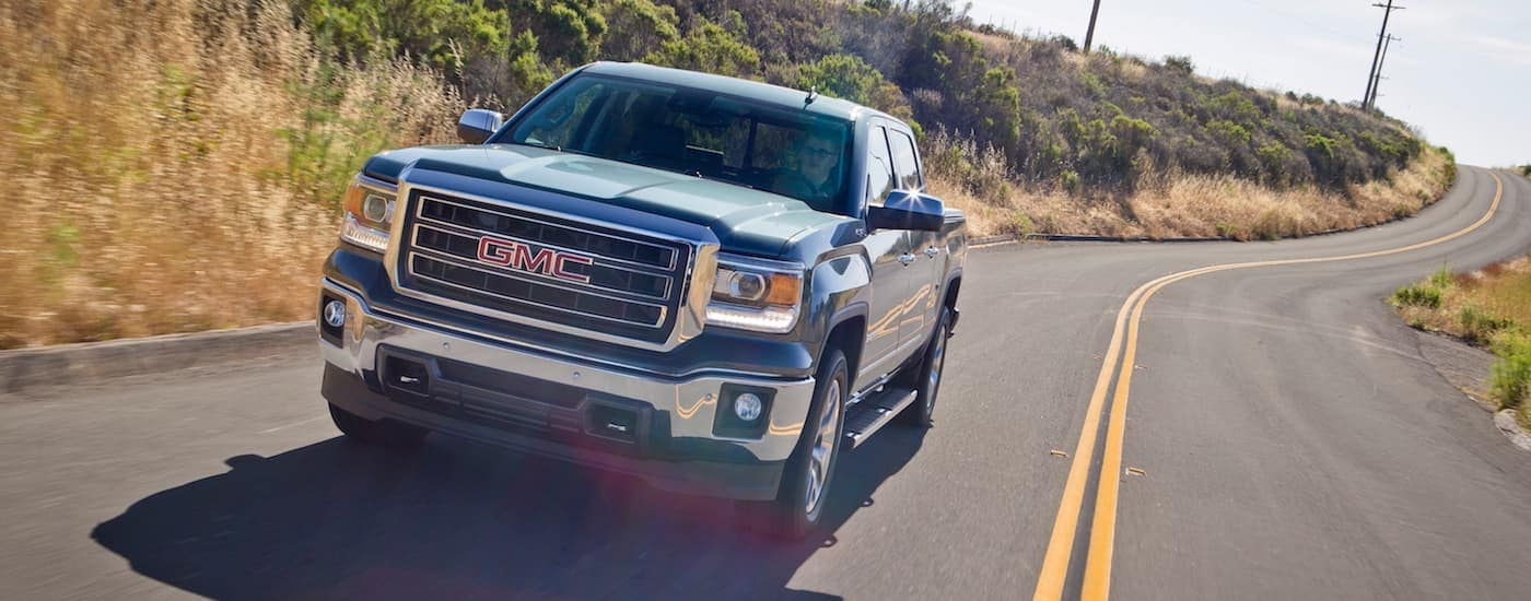 A popular used GMC truck, a blue 2015 Sierra, is driving down a highway.