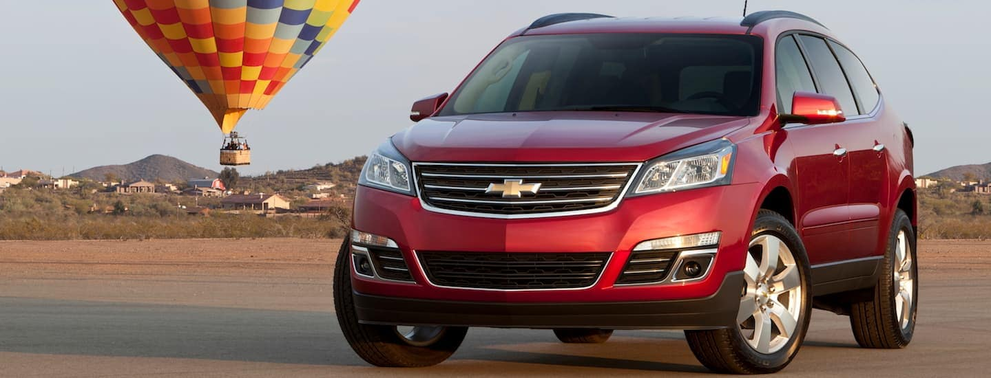 A red 2015 Chevy Traverse, which is a popular used SUV for sale, is parked in front of a hot air balloon.