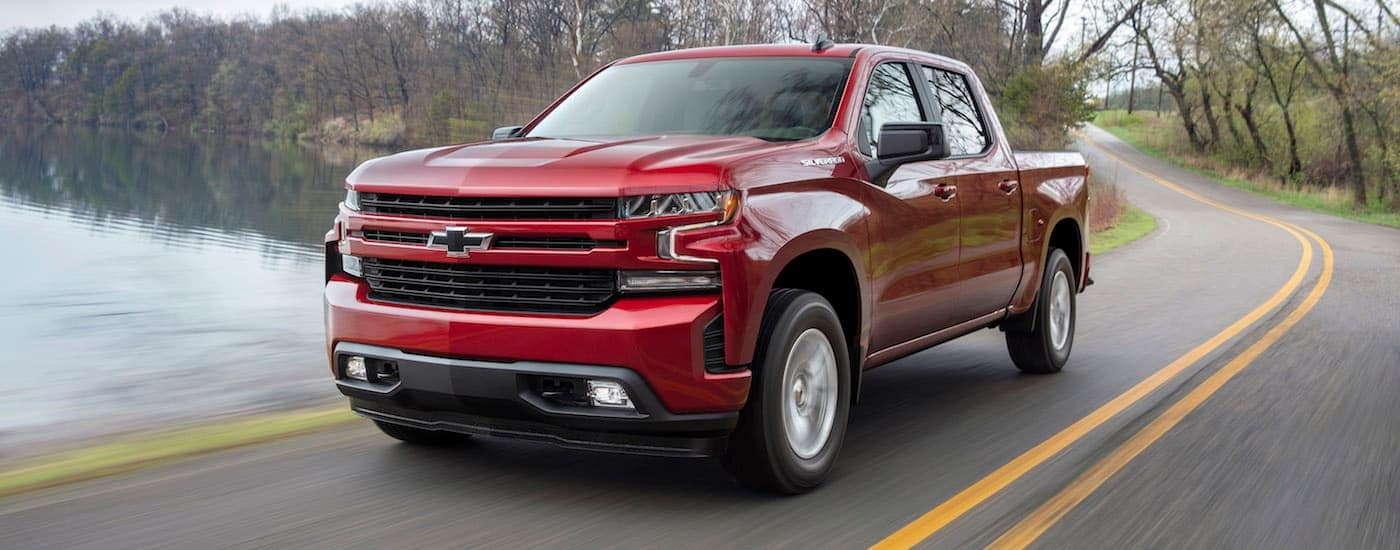 A red Chevy Silverado RST, a popular Chevy in Fort Worth, is driving by a pond.