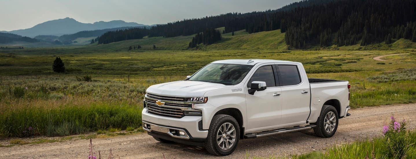 A white 2019 Chevy Silverado, popular among Chevy trucks in Corsicana, TX, is parked on a dirt road with mountains in the background.