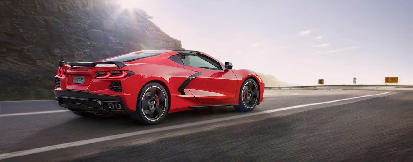 A red 2020 Chevy Corvette is driving towards a corner.