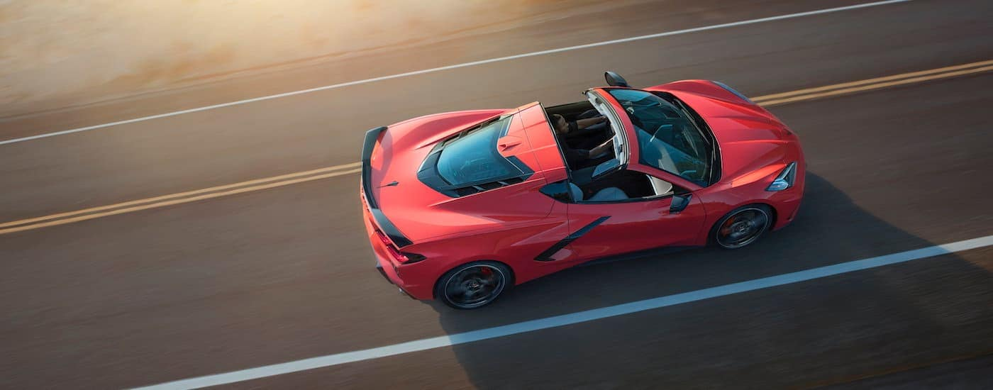 A red convertible 2020 Chevy Corvette is driving on a sunny highway near Fort Worth, TX.