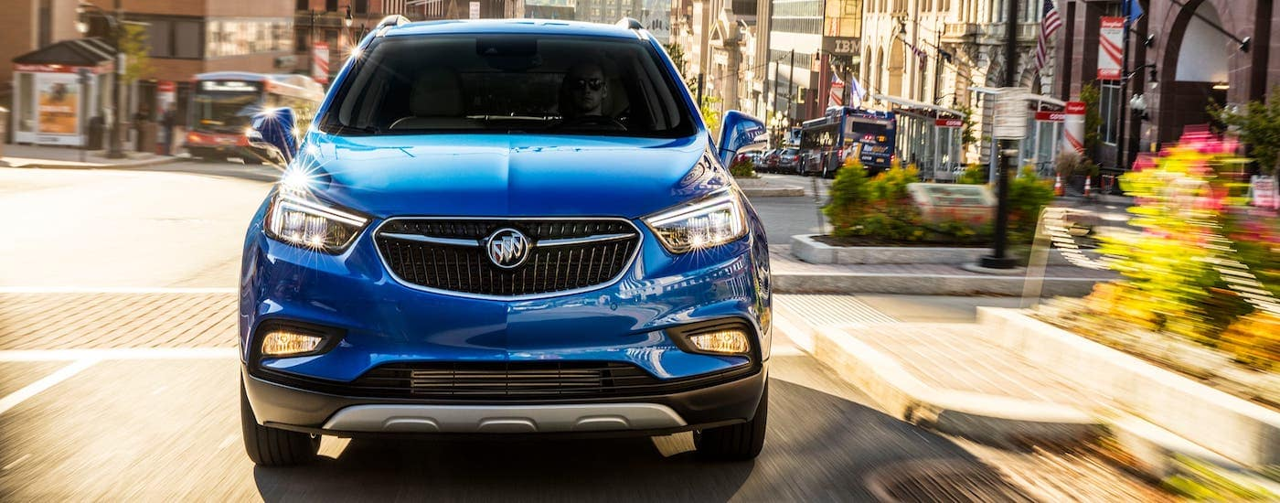 A blue 2020 Buick Encore is shown from the front driving on a city street.