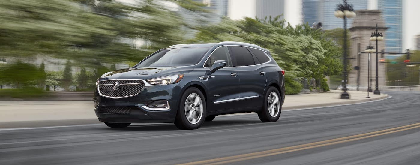 A gray 2021 Buick Enclave is driving on a blurry street after leaving a Buick dealership.