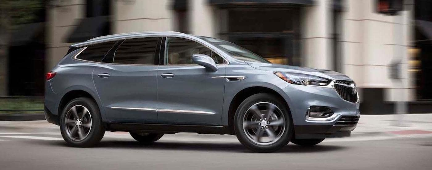 A light gray 2019 Buick Envision drives a buys city street.