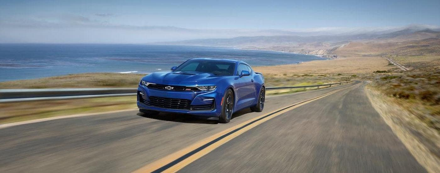 A blue 2020 Chevy Camaro is driving on a coastal highway.