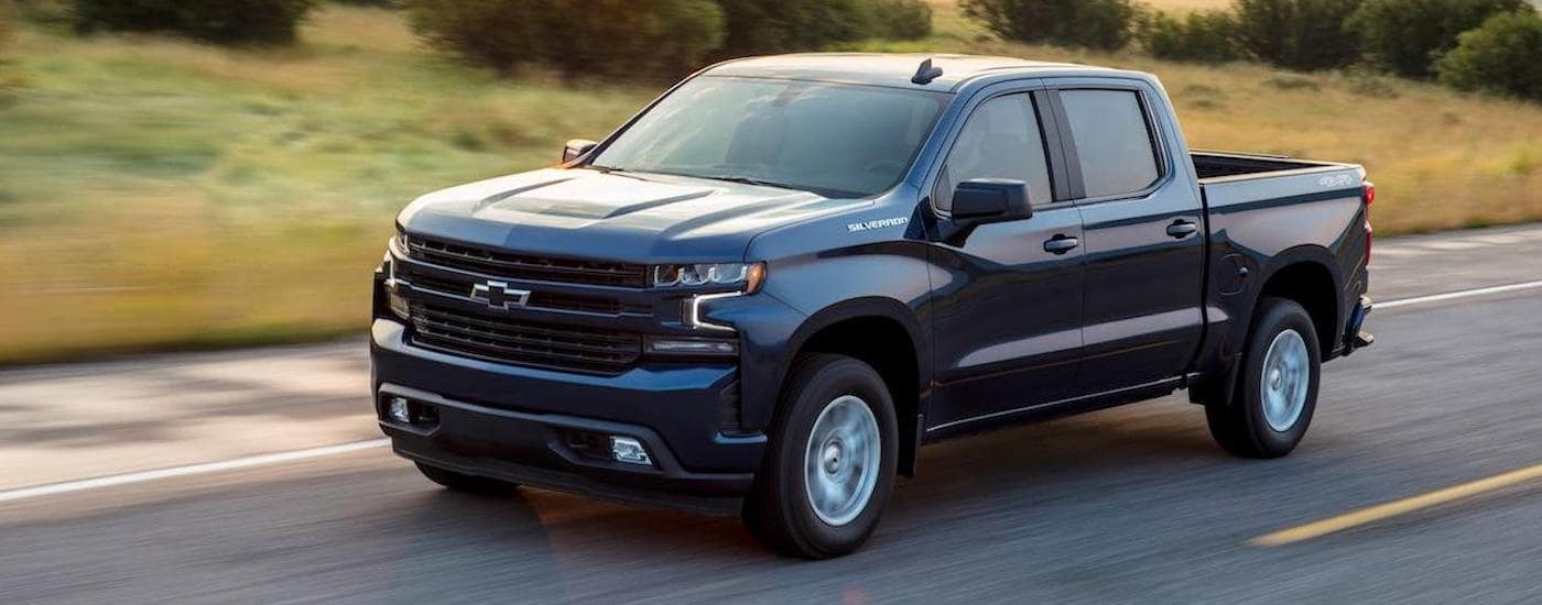A dark blue 2020 Chevy Silverado RST is driving on a desert highway. These trucks are popular Chevrolets in Fort Worth, TX.
