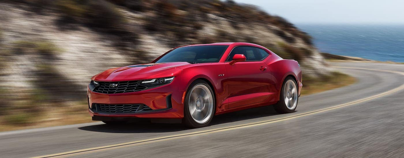 A red 2021 Chevy Camaro LT1, soon to be hitting a Chevy dealership near you in Corsicana, is shown driving on a coastal highway.