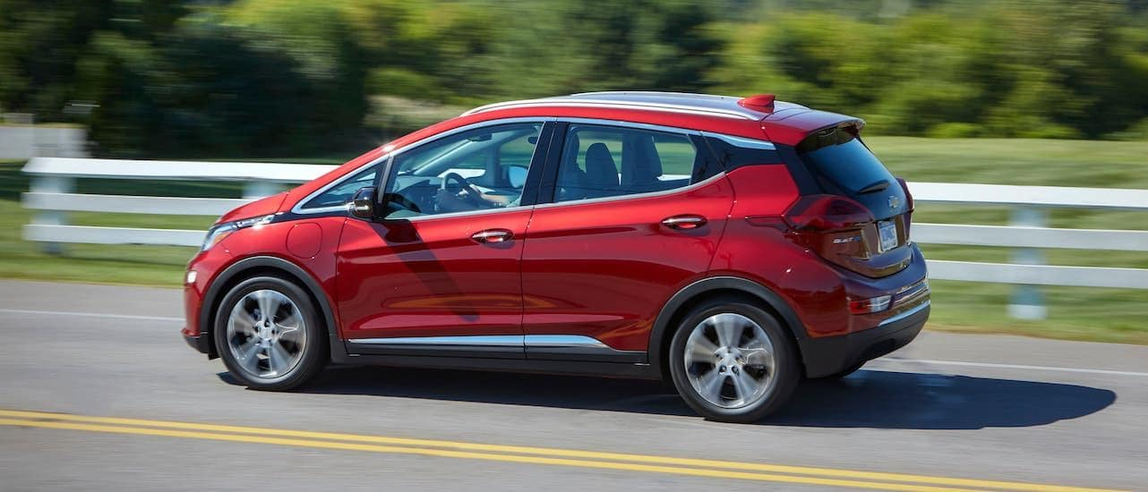 A red 2020 Chevy Bolt is driving in front of a white fence and shown from the side.