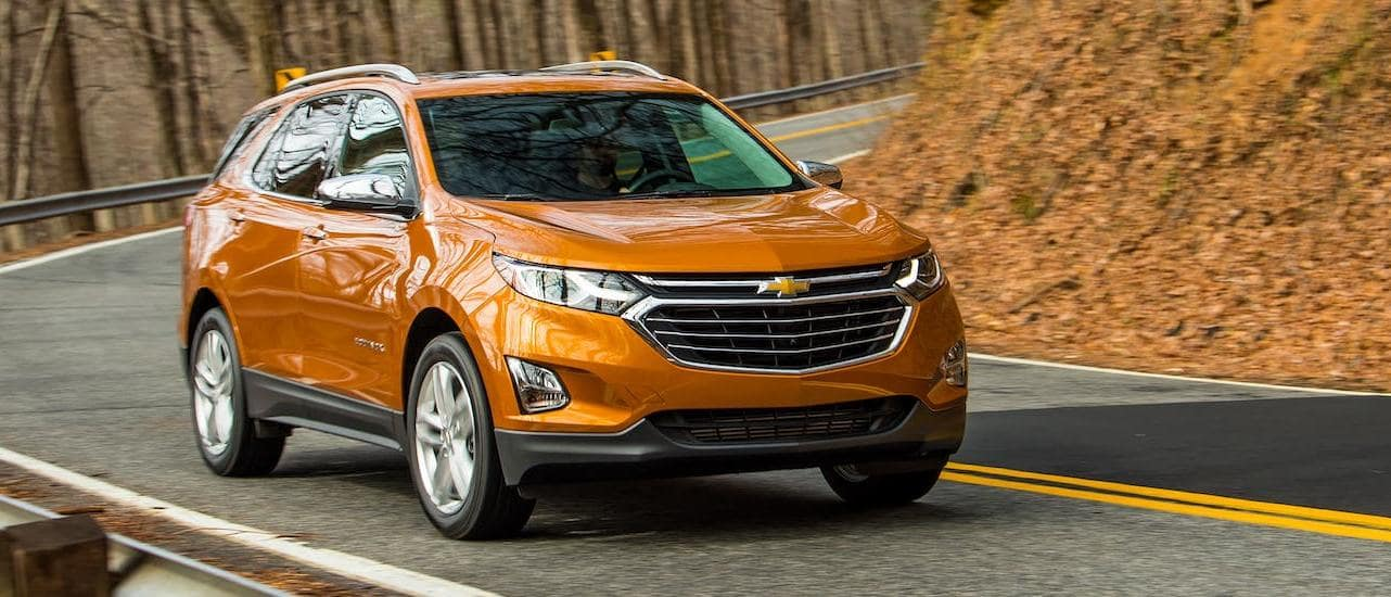 An orange 2020 Chevy Equinox from a Chevy Dealership Near you is driving around a corner.