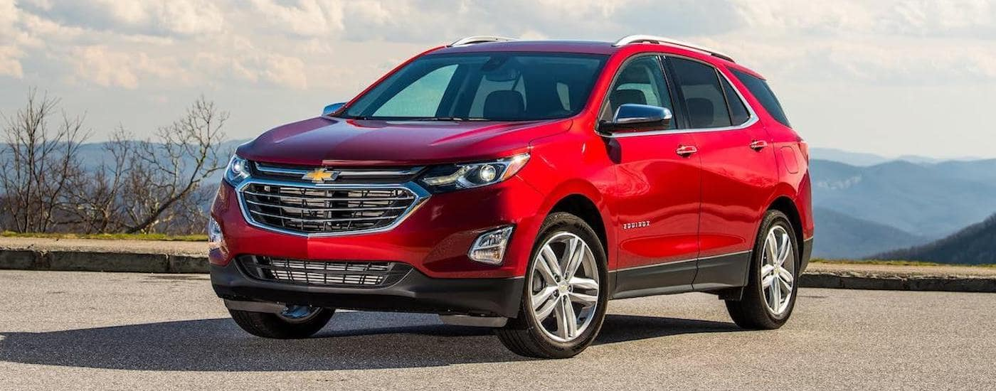 A red 2020 Chevy Equinox is in an empty parking lot overlooking mountains and a cloudy sky.