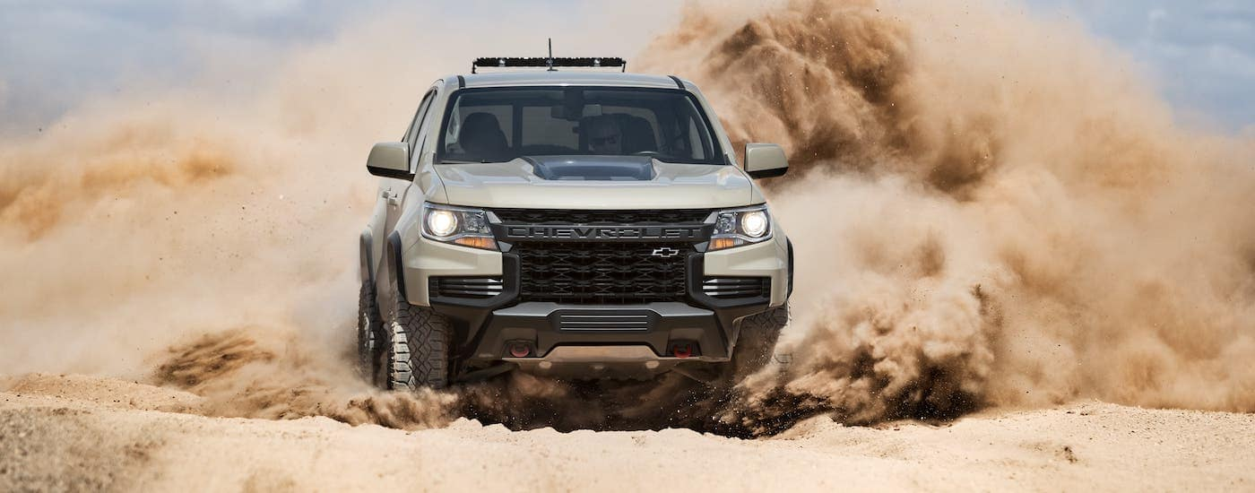 A tan 2021 Chevy Colorado is kicking up dirt clouds after leaving a Chevy Dealership near Waco, TX.