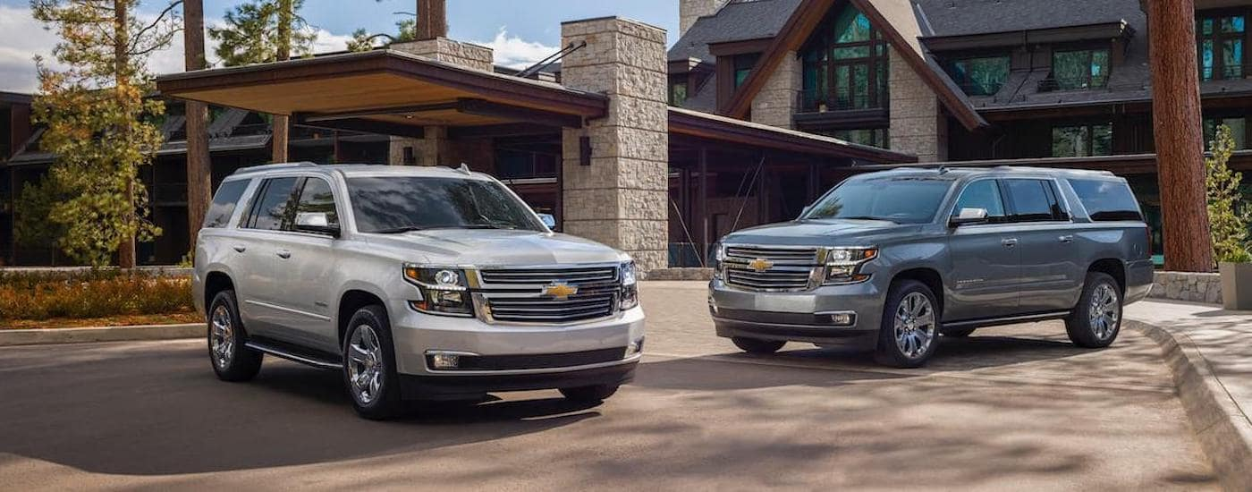 A silver 2020 Chevy Suburban, popular among Chevy SUVs, is parked next to a grey one outside a large home near Corsicana, TX.