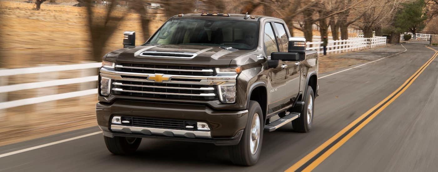A black 2020 Chevy Silverado 2500HD, available in the coming months at a Chevy Dealership, is driving past farm fencing near Corsicana, TX.