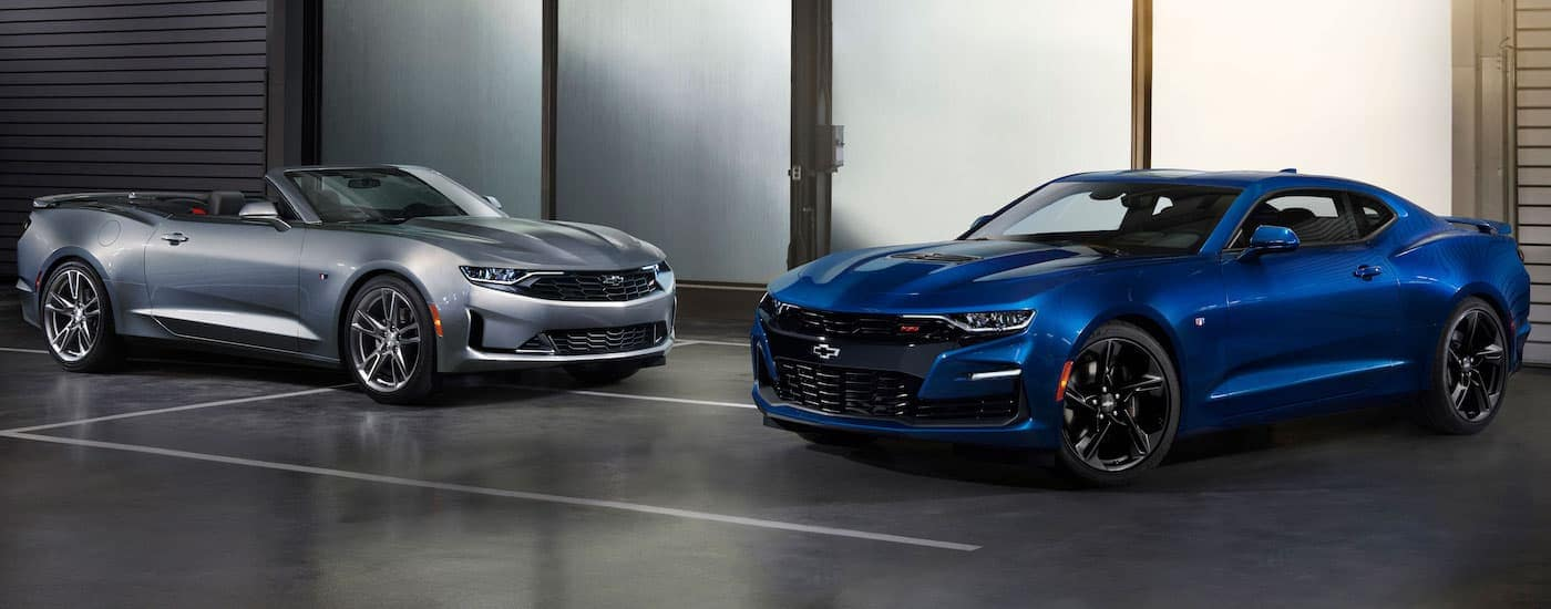 A grey 2019 Chevy Camaro convertible is next to a blue 2019 SS in a garage, both available at a Chevy dealership near me in Corsicana, TX.