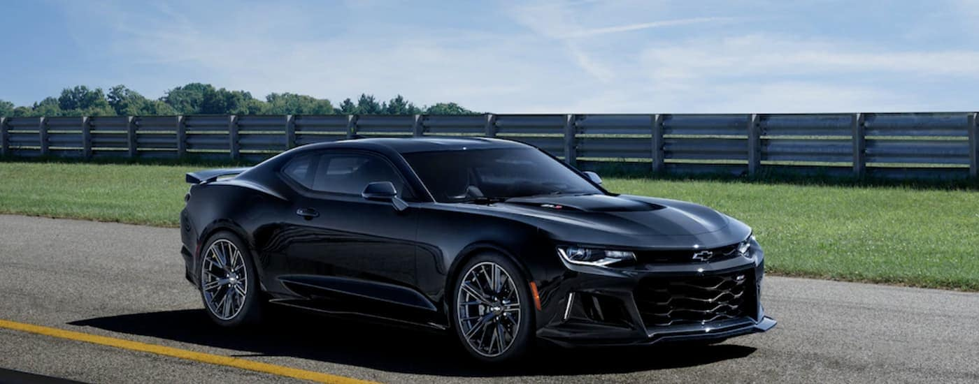 A black 2019 Chevy Camaro, a popular Chevy in Fort Worth, is parked near a fence line.