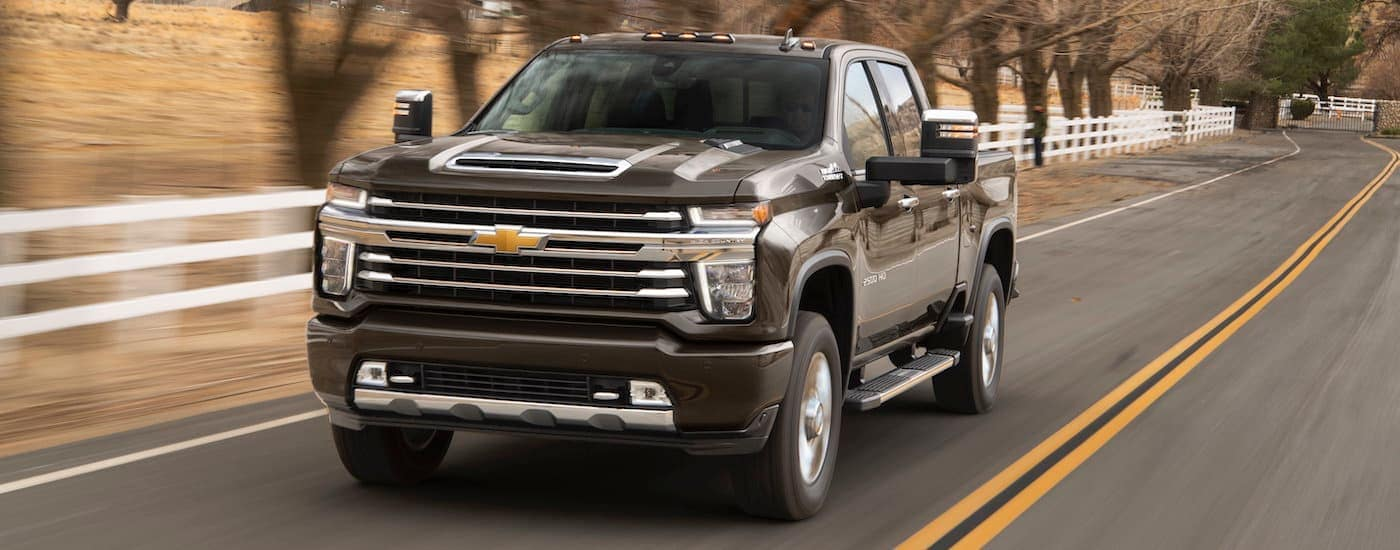A black 2020 Chevy Silverado 2500 HD, a popular choice for Chevy in Fort Worth, is driving past a farm.