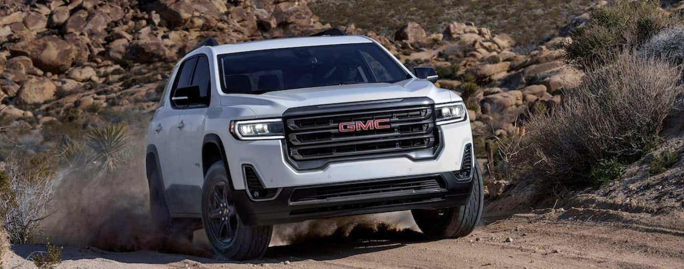 """A white 2020 GMC Acadia, which is a popular model you could find when you search """"GMC dealer near me,"""" is driving up a rock dirt hill near Corsicana, TX."""