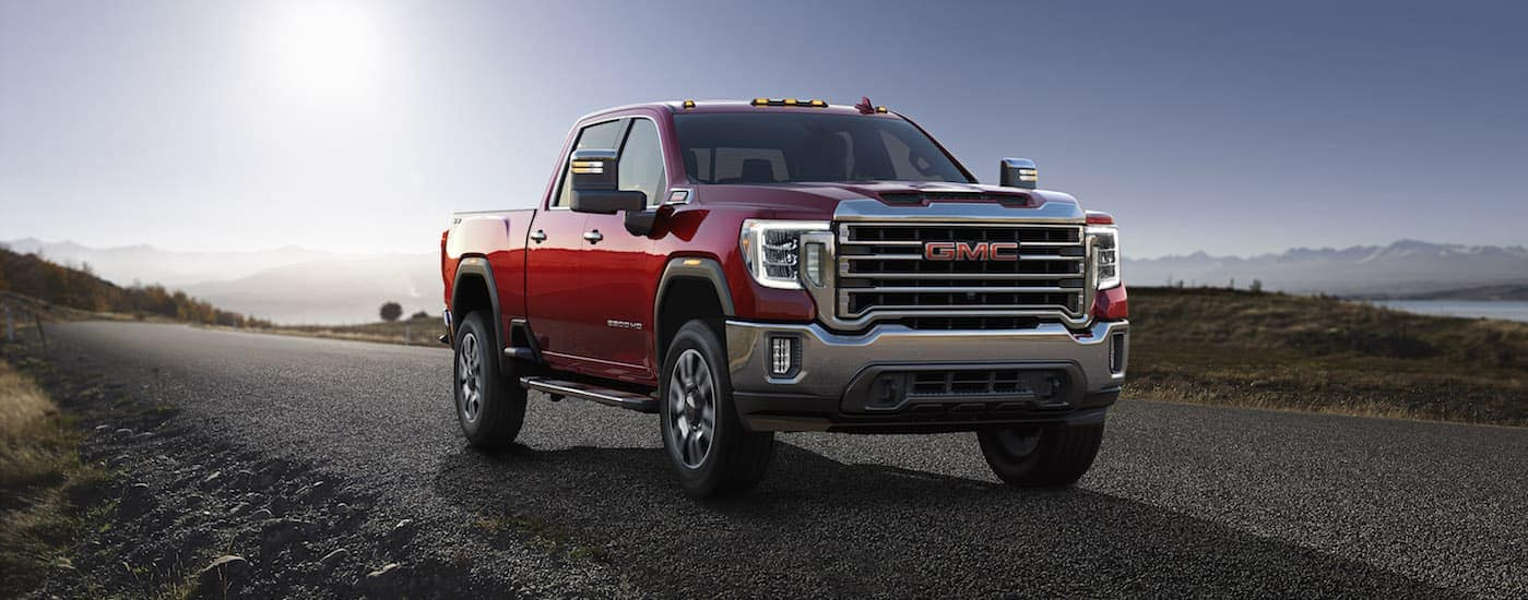"A red 2020 GMC Sierra 2500HD, which is a model you can find when you search ""GMC dealer near me,"" is parked on a grass lined road near Corsicana, TX."