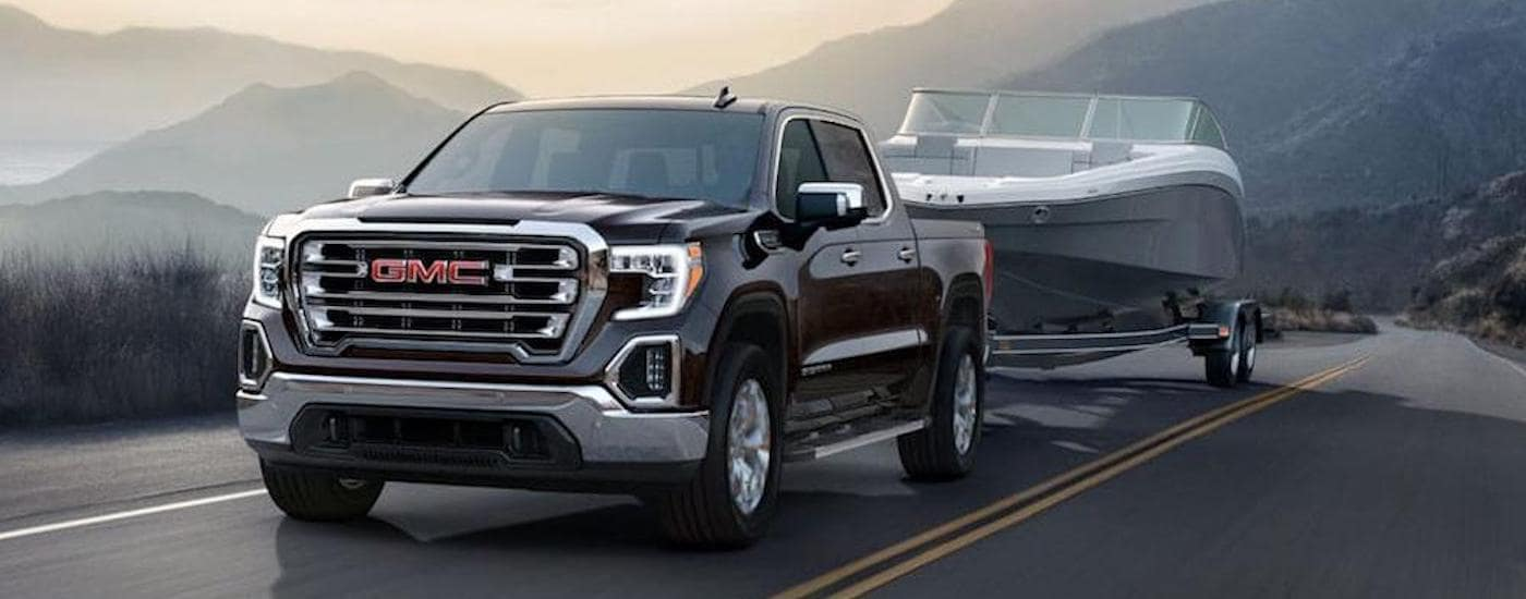 A black 2019 GMC Sierra is towing a boat in front of mountains after leaving a GMC dealer near me.