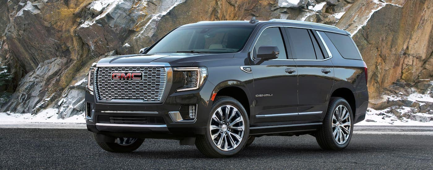 A gray 2021 GMC Yukon Denali from a GMC dealer near Waco is parked in front of a rock face.