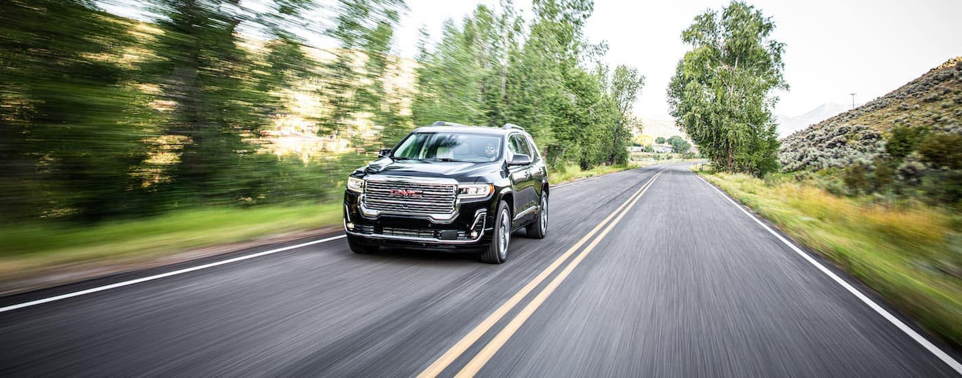 A black 2020 GMC Acadia, popular among GMC SUVs, is driving along a blurry, tree-lined road near Corsicana, TX.
