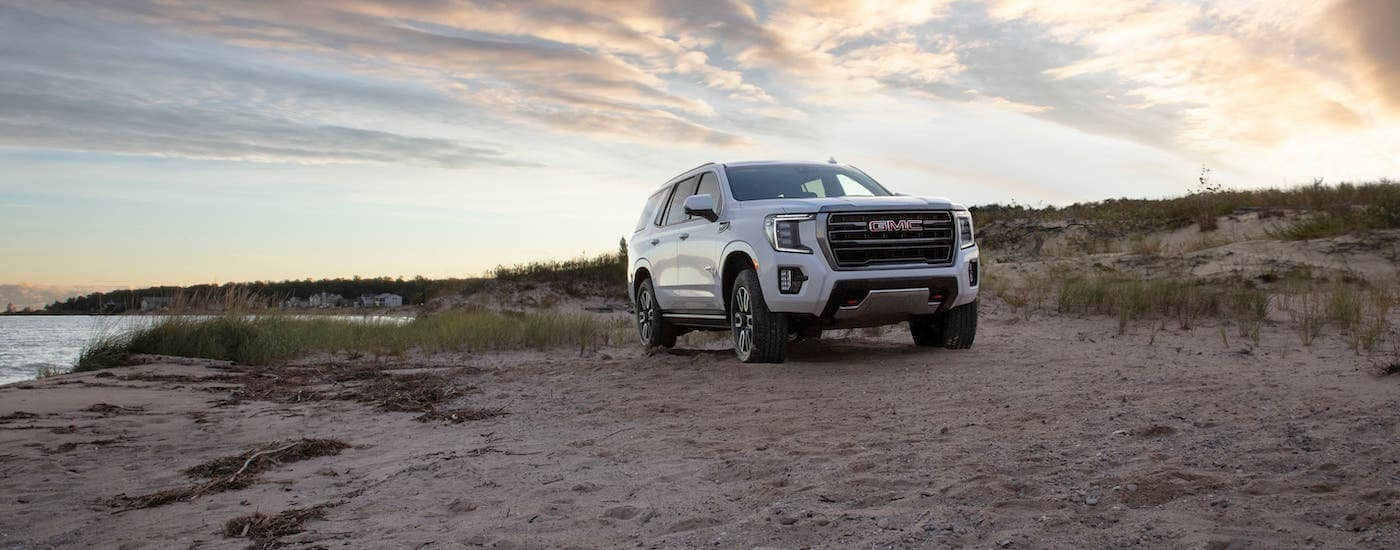 A white 2021 GMC Yukon AT4 is parked on a beach in front of cloudy sky at sunset.