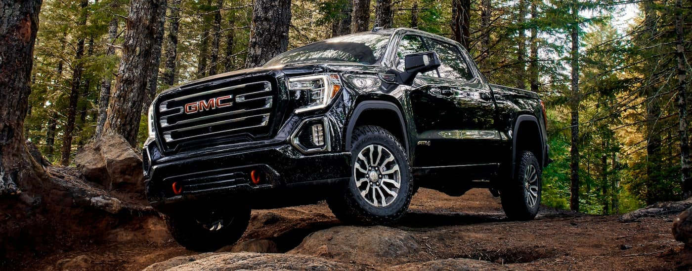A black 2019 GMC Sierra AT4 is on a trail in the woods outside of Corsicana, TX.